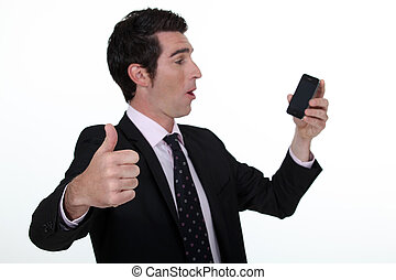 Thumbs up from a businessman with a cellphone