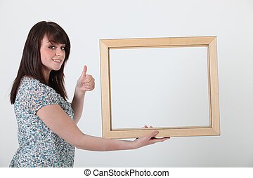 Thumbs up from a woman with a frame