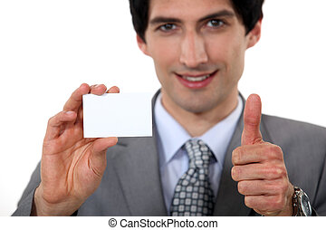 Thumbs up from an executive holding a blank business card