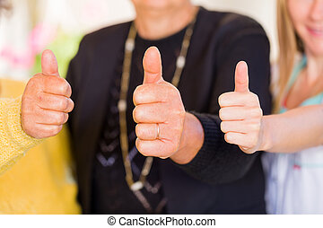 Thumbs up - Photo of elderly women with their carer showing...