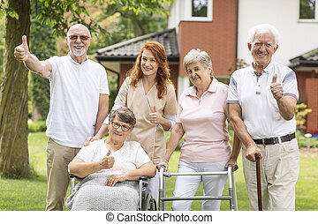 Thumbs up shown by happy female and male seniors and a caregiver outside their nursing home.