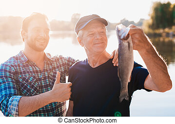 Thumbs up. The old man is holding a fish. A man stands behind him with his thumb up