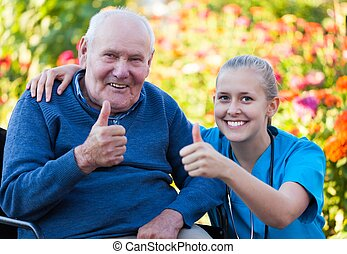 Young happy doctor showing thumbs up with his elderly patient.