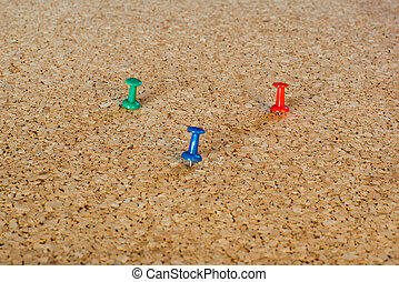 Thumbtack pins on pinboard - 3 coloured thumbtack pins on...