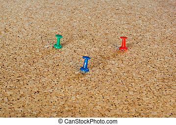 Thumbtack pins on pinboard - 3 coloured thumbtack pins on...