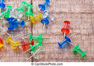 thumbtacks of colors on old wood top view