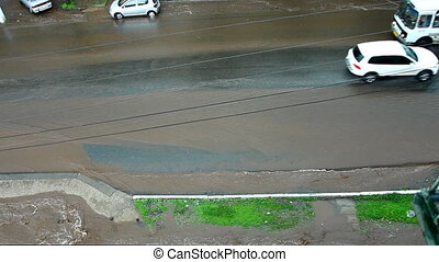 thunderstorm in city - cars move on road with flood