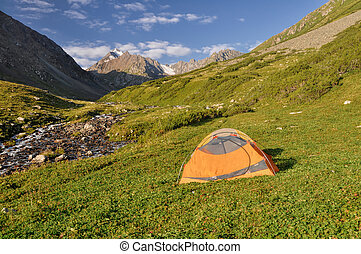 Hiker's tent on a slope in Tian-Shan Mountains, Kyrgyzstan