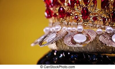 collection of tiaras decorated with gemstones and headband with pearls turn on yellow color background extreme closeup