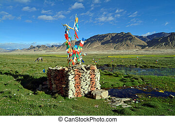 Tibet - stone heaps with prayer flags on pasture landscape...