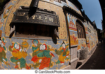 Tibetan art murals on building wall in Dayan old town.