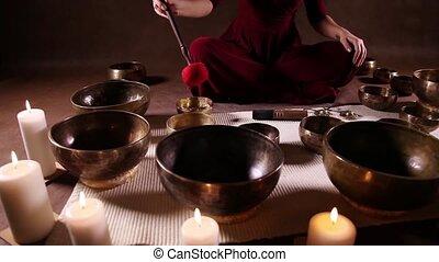 Tibetan bowls dolly shot - Woman playing Tibetan singing...