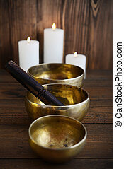 Tibetan handcrafted singing bowls with sticks on wooden...