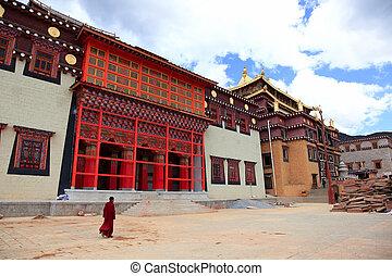 Tibetan monk is walking in Songzanlin Monastery in Zhongdian...