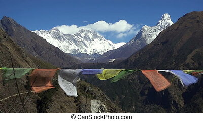 Tibetan prayer flags against white snowy mountain peak in...