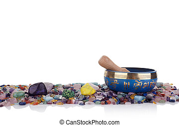 tibetan singing bowl and multicoloured healing chakra stones against a white background