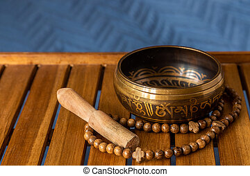 Tibetan singing bowl and rosary on a wooden stand