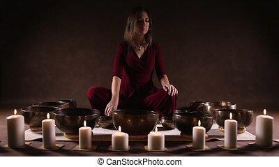 Tibetan singing bowl - Woman playing Tibetan singing bowl in...