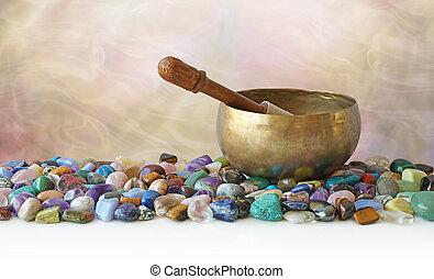 Tibetan Singing Bowl surrounded by tumbled healing stones