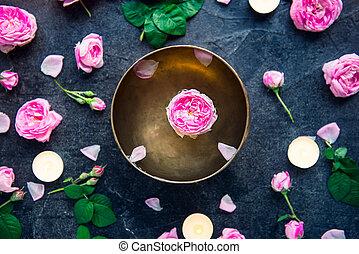 Tibetan singing bowl with floating rose inside. Burning...