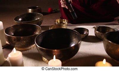 Tibetan singing bowls dolly shot - Woman playing small...