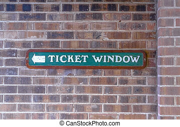 Ticket Window sign against a brick wall