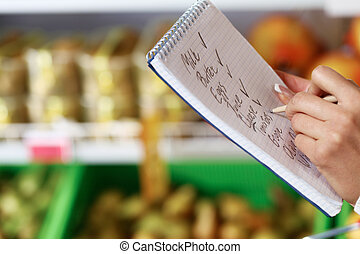 Ticking names of products - Image of female hand with pen ...