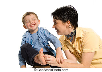 Tickle - mom tickling son's feet on white isolated ...