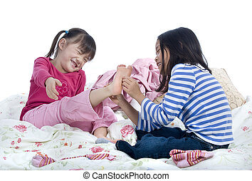 Tickle toes - Two sisters playing on the bed tickling toes