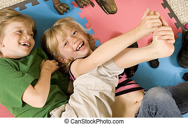 Tickling! - Adorable twins playing tickle on the floor.