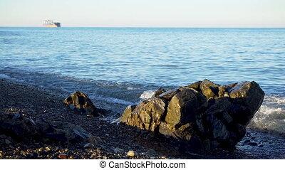 Tidal bore on stony pebble sea shore with foamy waves and ...