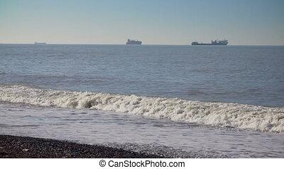 Tidal bore on stony pebble sea shore with foamy waves and...