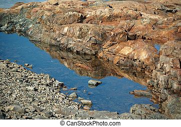 Reflection of rocks in a tidal pool