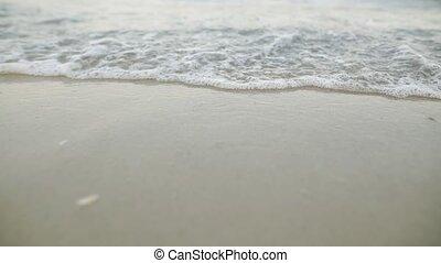 Tidal wave on a clean, sandy, sea beach. Above eye level...
