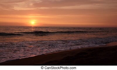 Tidal waves of the sea in beams of a pink sunset - Tidal...