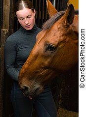 Woman give a tidbit to horse, vertical format