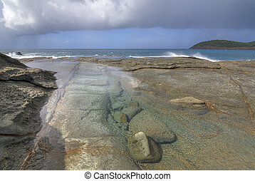 Tide pool on rocky Caribbean shore with rain at sea