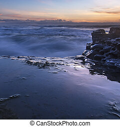 Tide pools in the ocean at sunset in San Diego