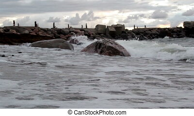 Tides coming in the rocky shore. The waves of the sea are...