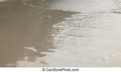 Tides reaching the shore - Tides reaching the sand on the...