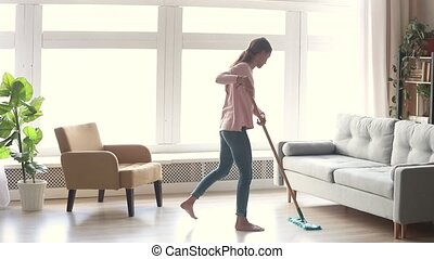 Tidy young woman housewife clean floor in modern living room