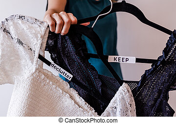 tidying up and decluttering conceptual still-life, woman holding clothes hangers with black and white tops and text labels to sort between items to Keep and Declutter shot at shallow depth of field