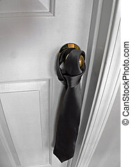 Tie On Doorknob - A necktie hangs from a doorknob. This room...