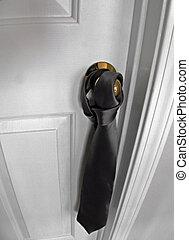 Tie On Doorknob - A necktie hangs from a doorknob. This room...