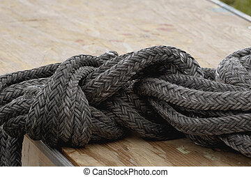 Tied in knots - Faded black nylon rope tied in knot lying...