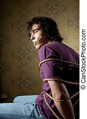 Tied man - An image of a young tied man on a chair