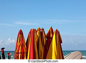 Tied up beach umbrellas by seaside