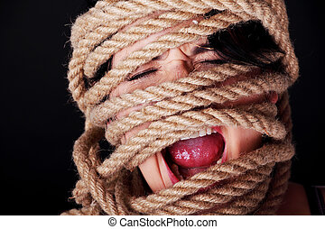 Tied up woman screaming. Violence concept.