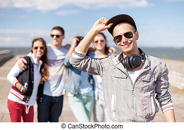 tienerjongen, met, zonnebrillen, en, vrienden, buiten