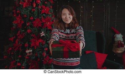 tient, noël, dehors, rouges, girl, present., appareil-photo., arbre, asiatique, présentation, présent, beau, jeune, bows., décoré